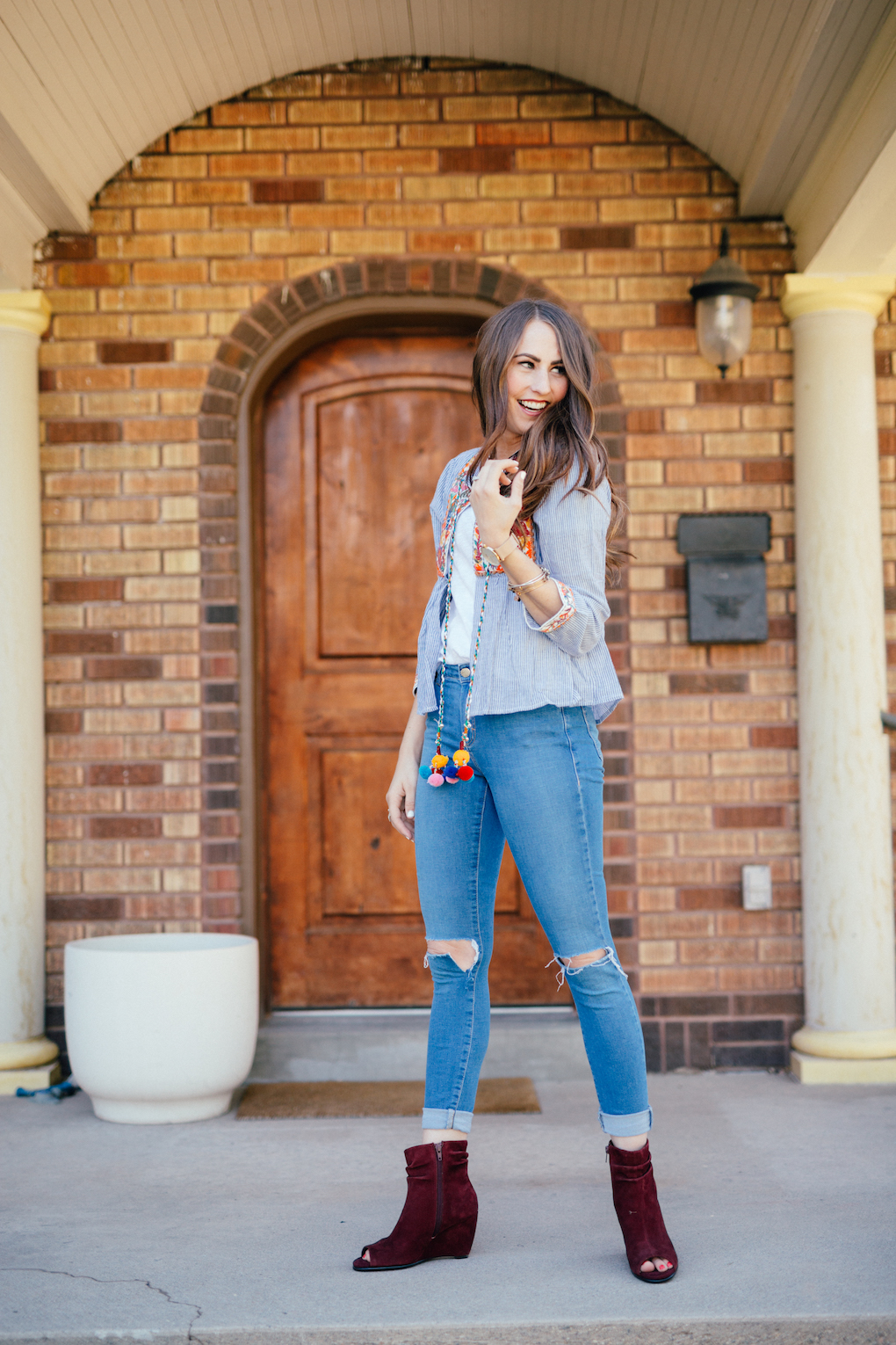 Girl standing at front door with blue stripe jacket with pom pom tassels distressed jeans and maroon wedges