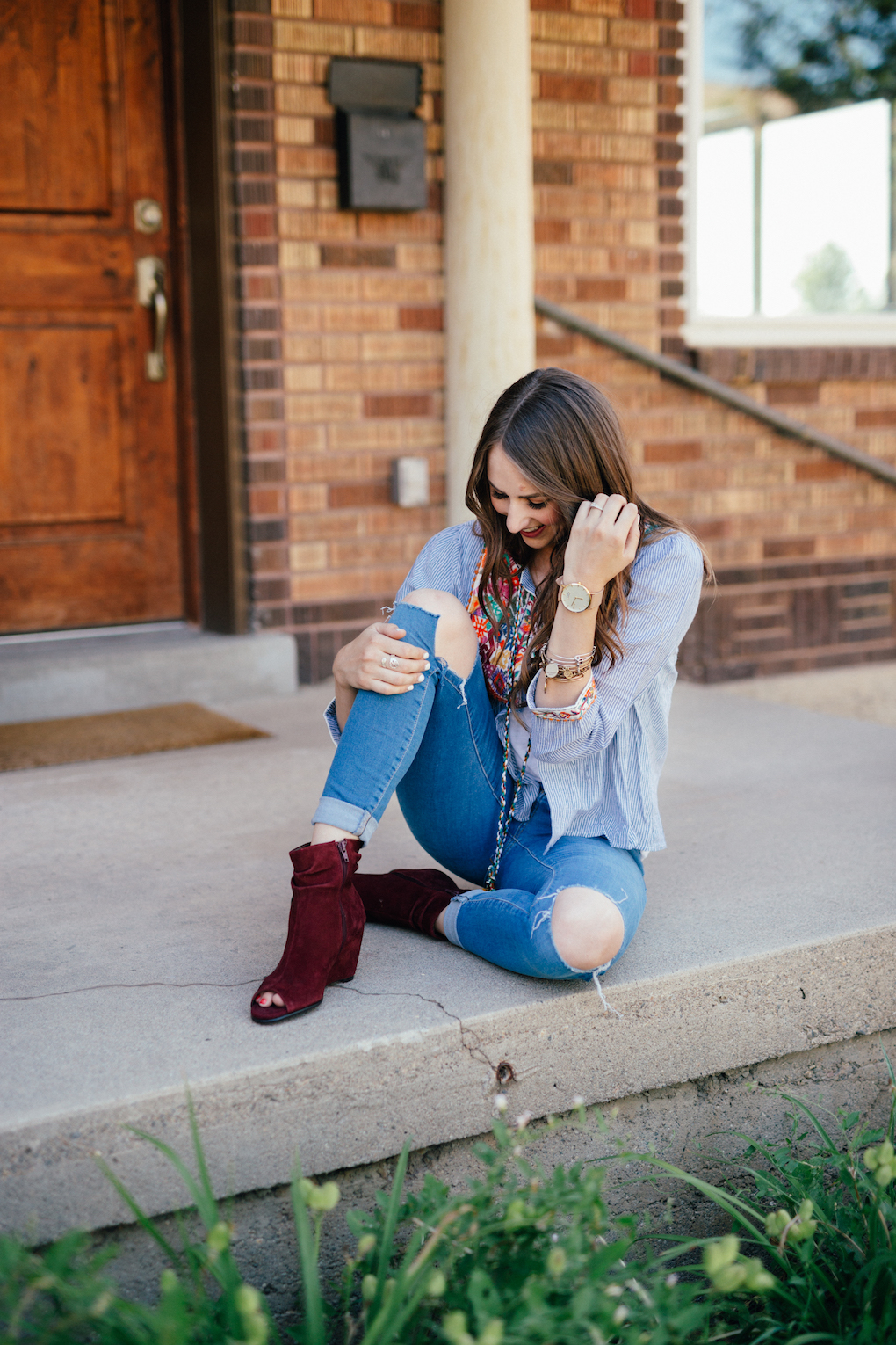 Girl sitting at front door with blue stripe jacket with pom pom tassels distressed jeans and maroon wedges