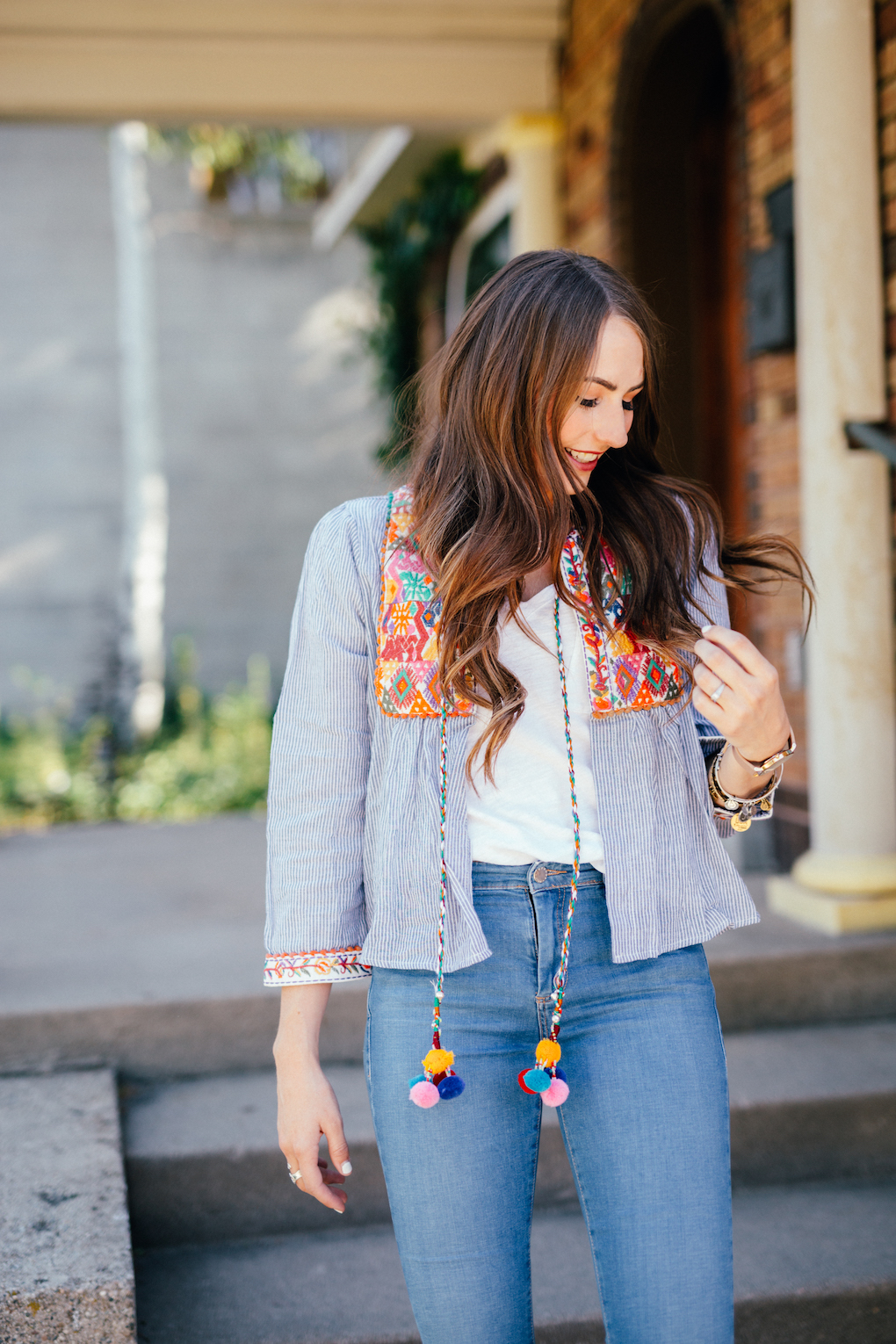 Girl with loose brown hair wearing distressed denim jeans and blue stripe embroidered jacket with pom pom tassels