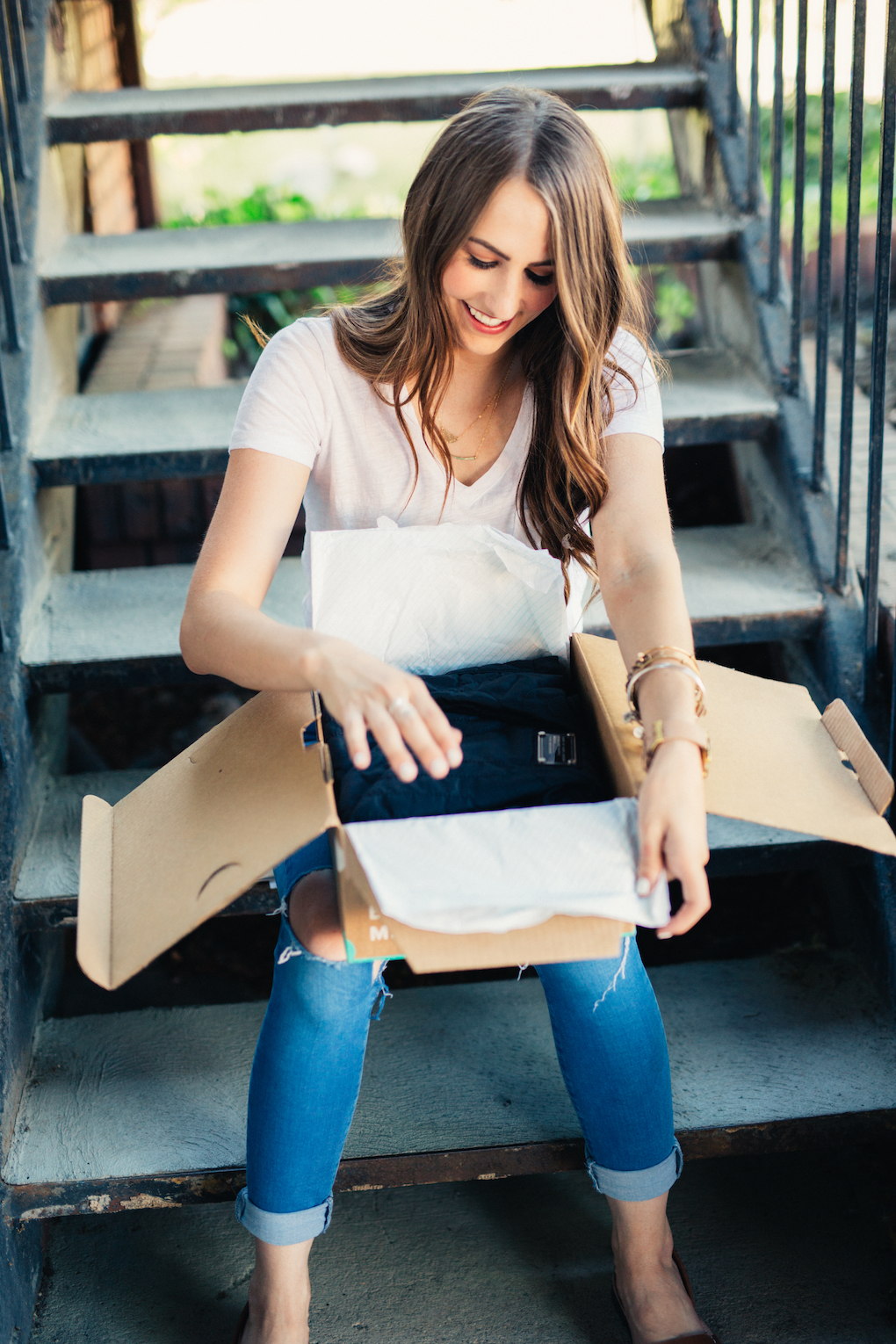 Girl with long brown curled hair in white madewell v-neck unboxing thredup box