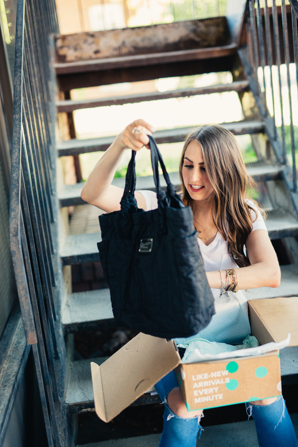Girl with long brown curled hair in white madewell v-neck unboxing thredup box marc jacobs bag