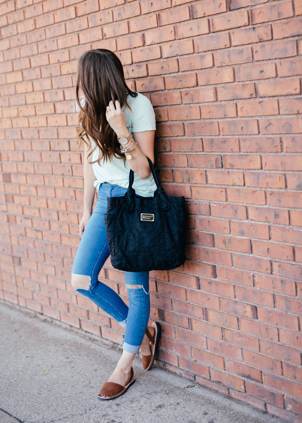 Girl with long brown curled hair wearing distressed skinny jeans, mint madewell tee, marc jacobs bag, and PONS shoes