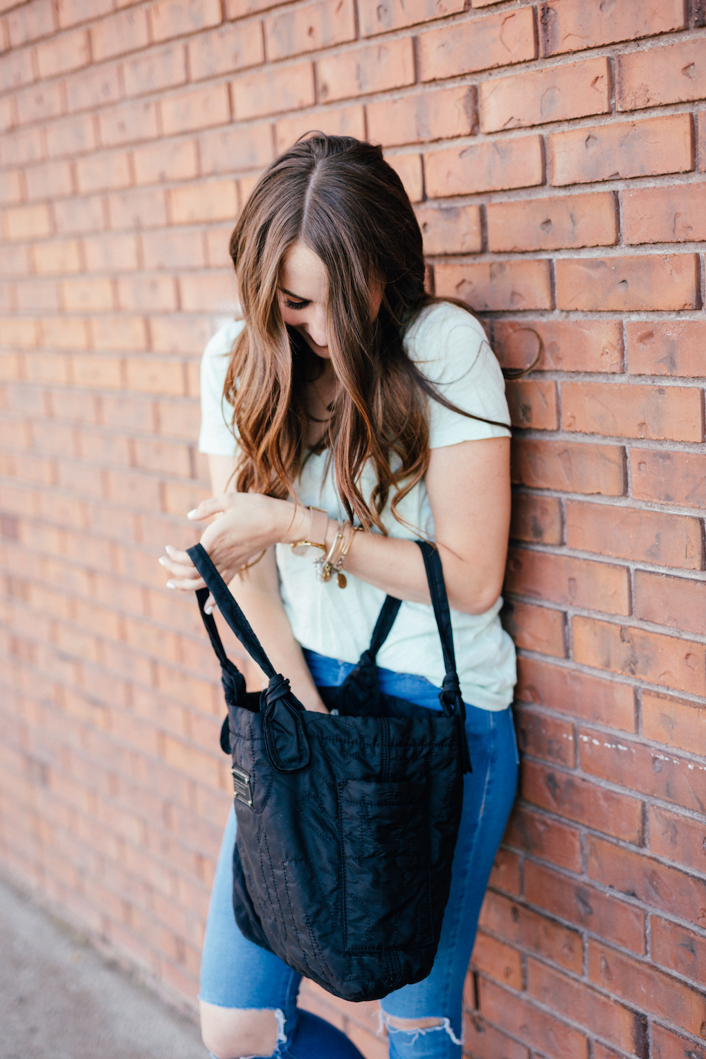Girl with long brown hair looking in black marc jacobs bag
