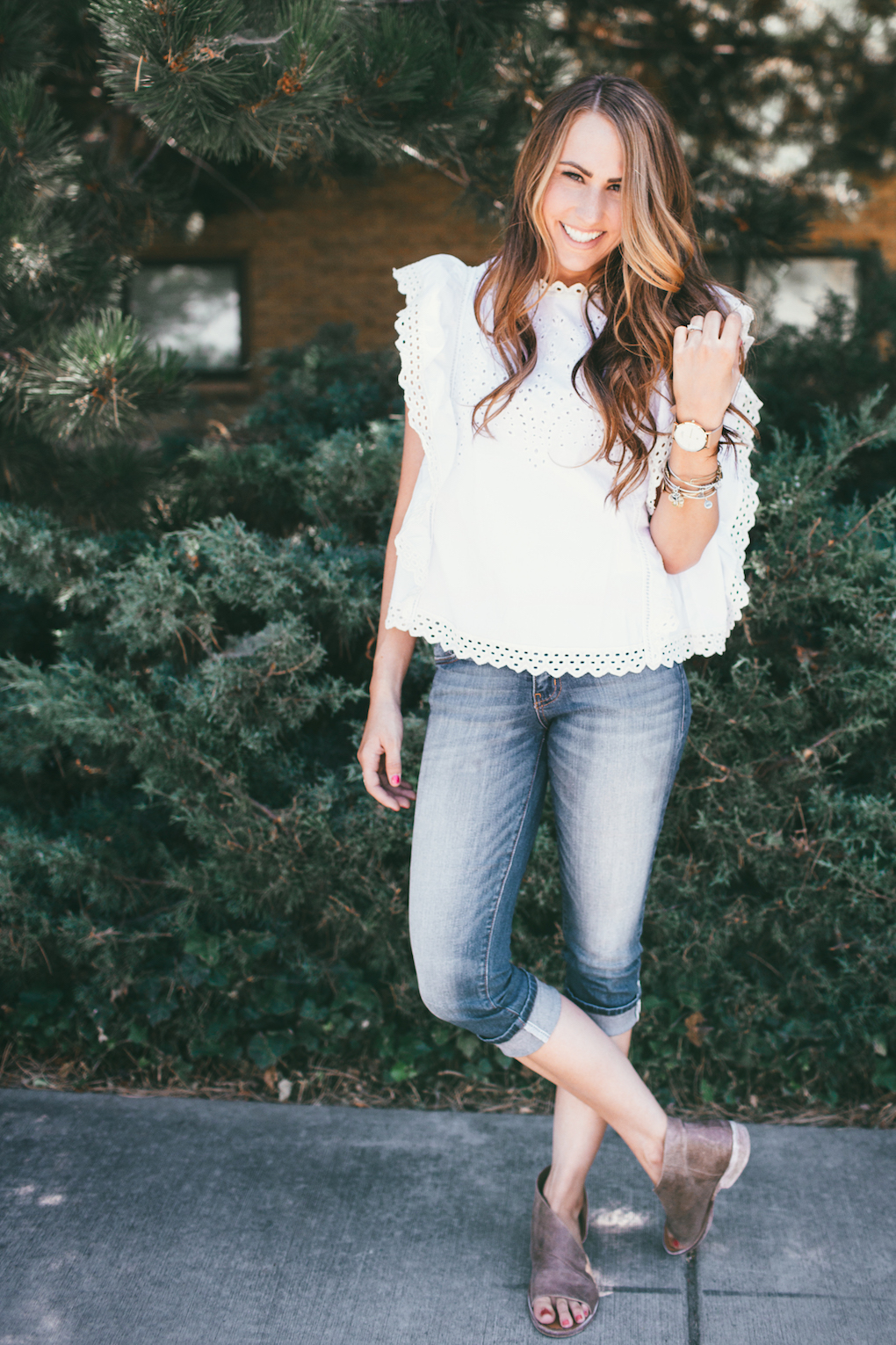 Girl in white eyelet top with crops on with watch and bracelets