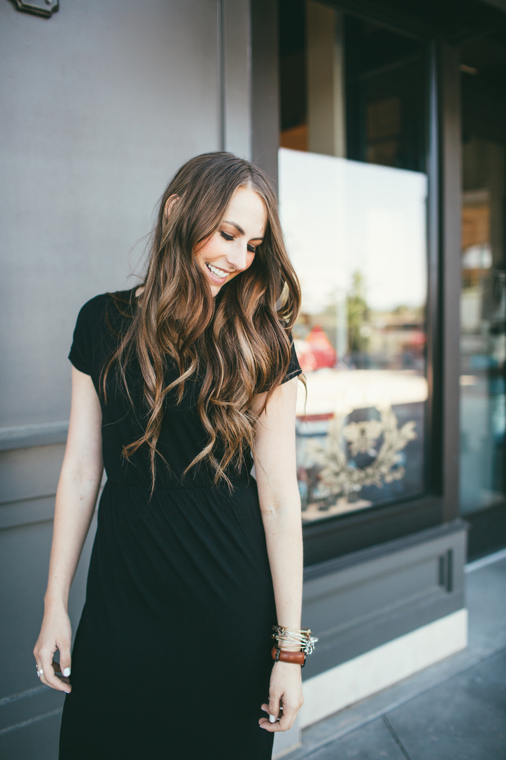 girl wearing black dress with rouched waist with long brown loosely curled hair looking down with eyes closed