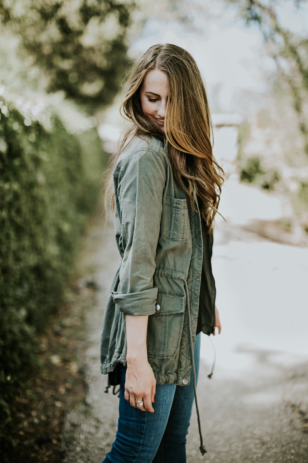 girl looking down with eyes closed wearing green army jacket with the sleeves rolled and loose curled brown hair