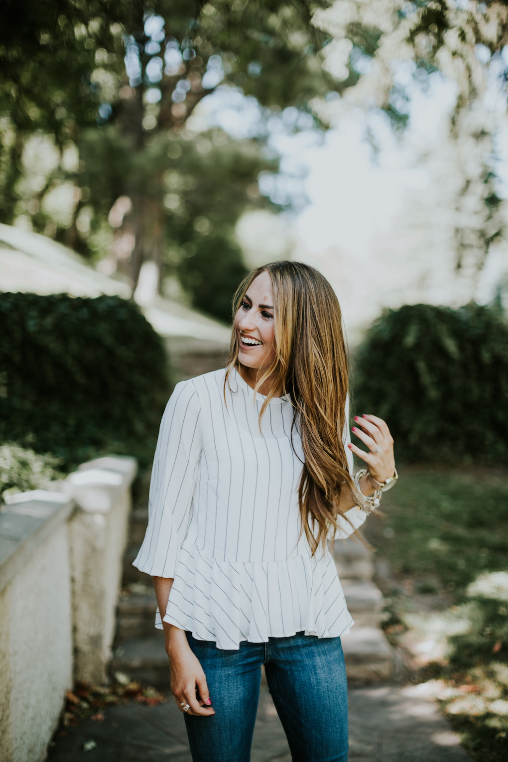 girl laughing wearing black and white stripe peplum top that is oversized and high waisted denim jeans