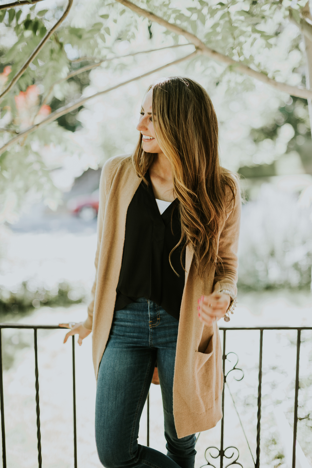long loose curled brown hair with girl wearing long oversized tan cardigan and black sheer top