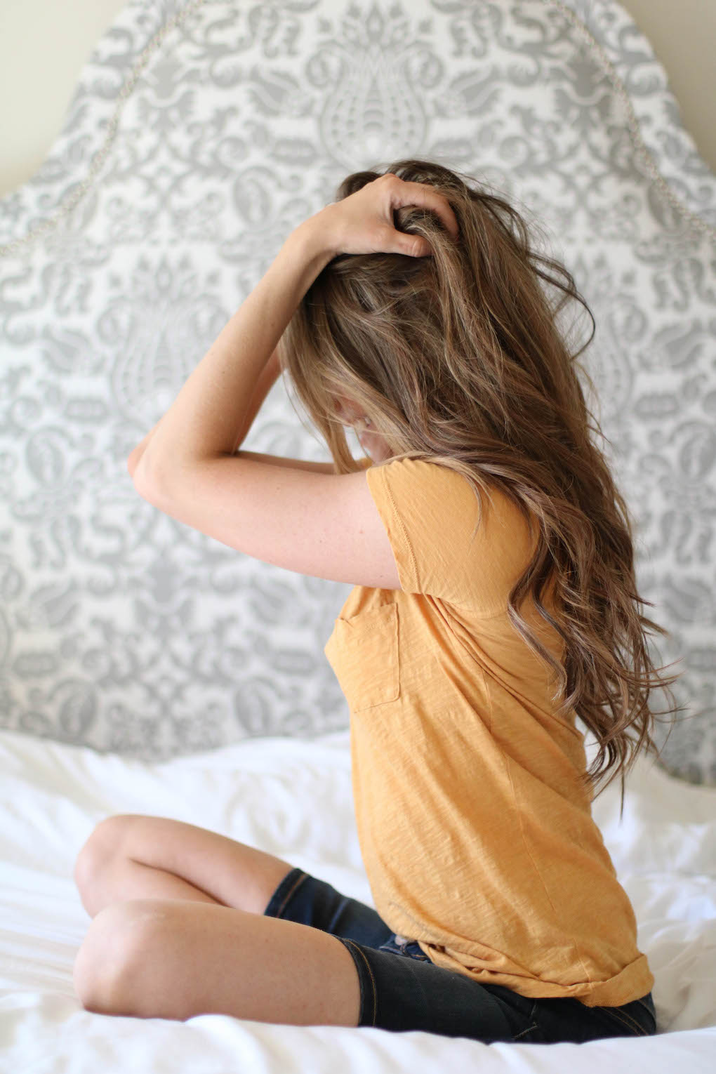 Girl in yellow tee with caramel highlights in brown hair and long curls