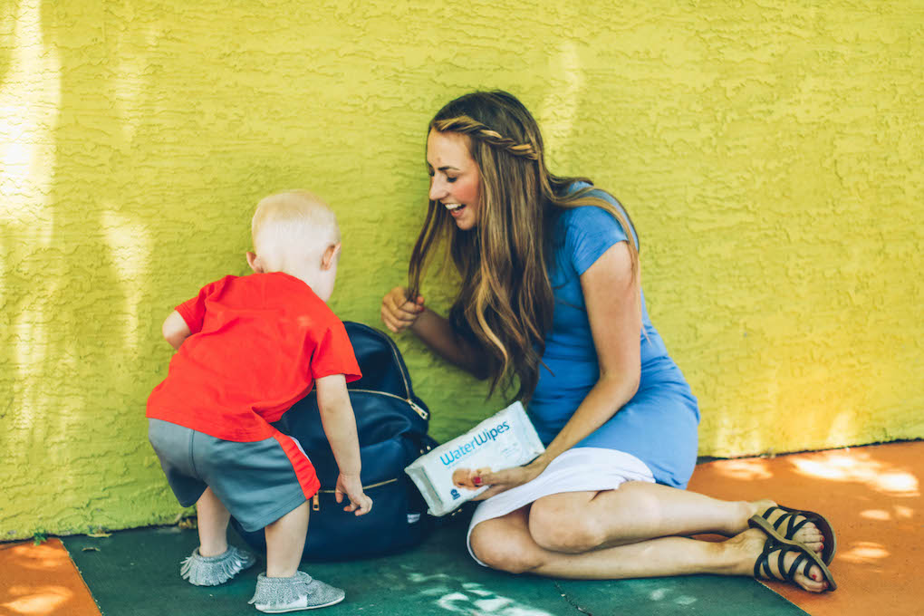 mom and baby sitting on green concrete in front of yellow wall talking and emptying diaper bag with water wipes