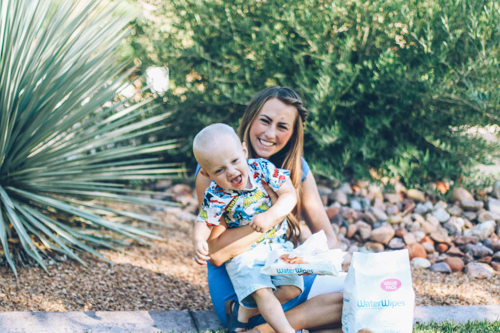 Mom and baby giggling on grass baby wearing a super hero tee with water wipes