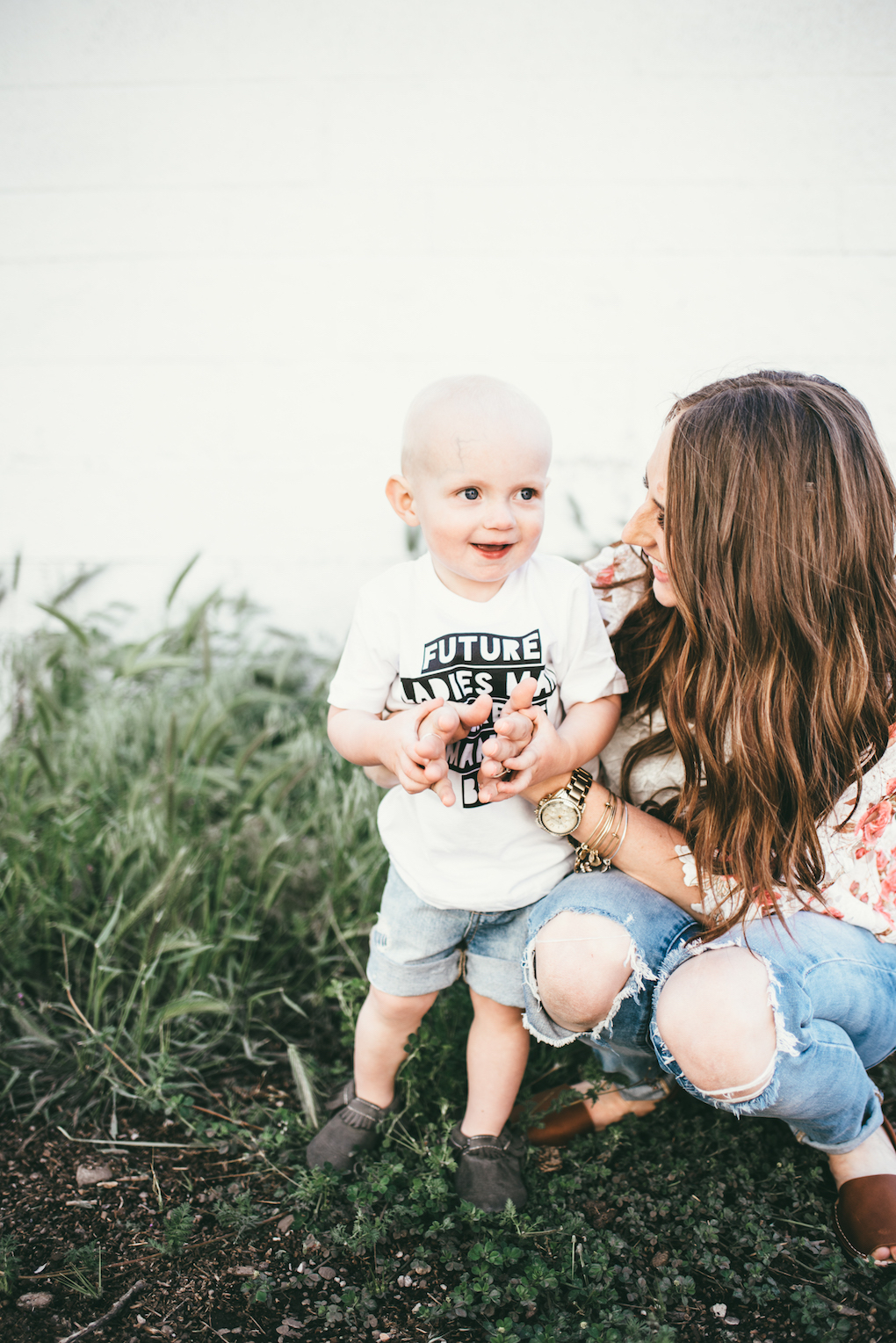 little boy in white graphic tee in cut off denim shorts with his mom