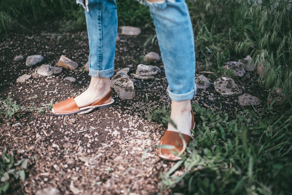 woman standing in dirt wearing distressed denim and brown pons shoes