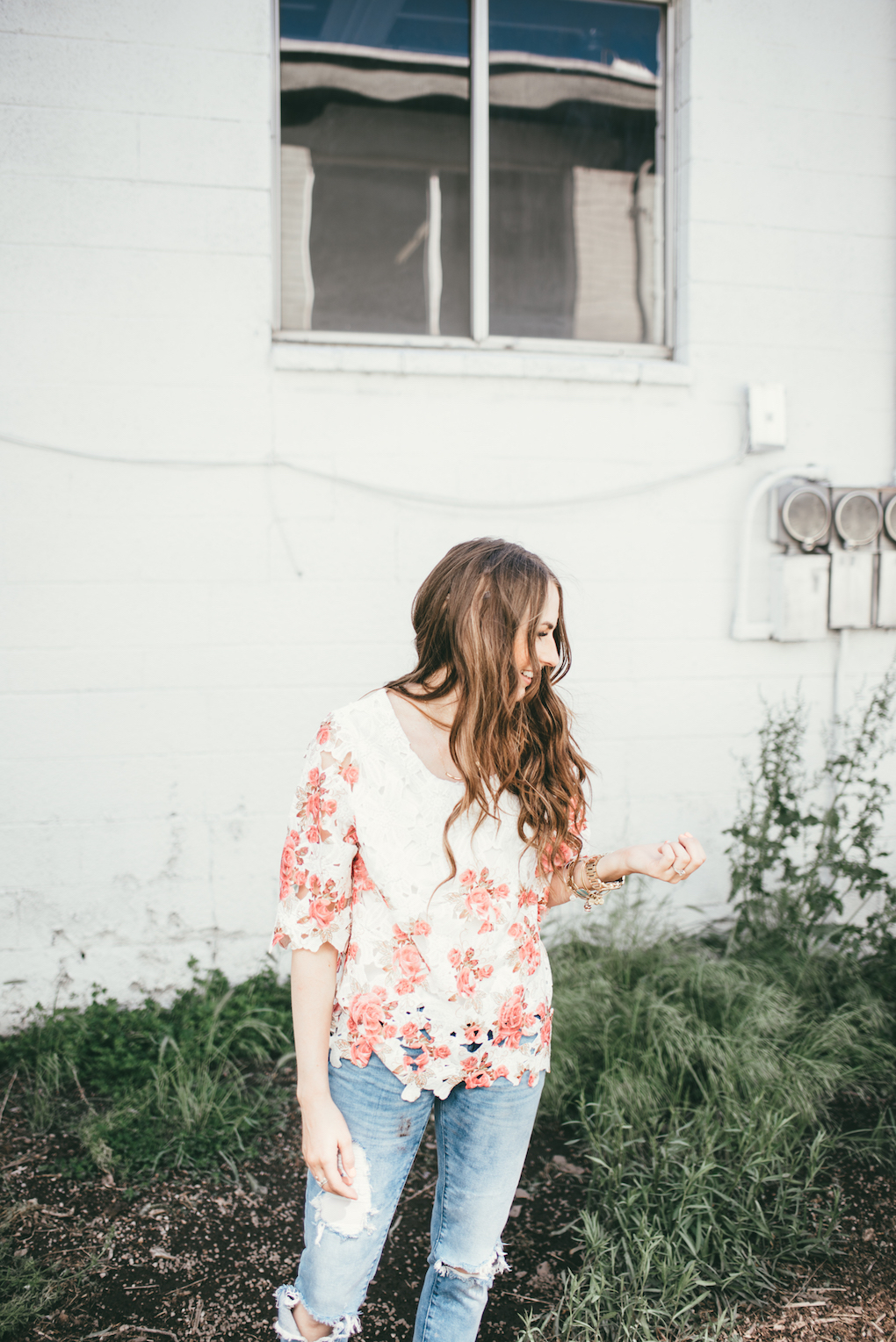 women standing in patch of greenery wearing distressed denim and pink and white lace top