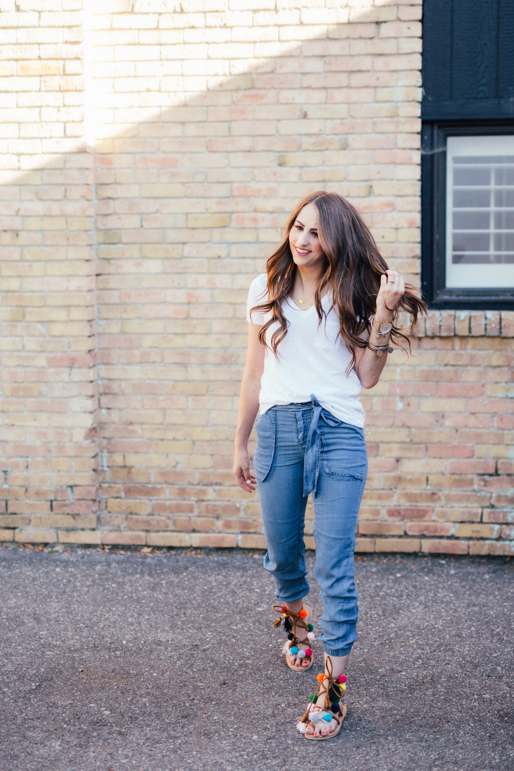 Denim Joggers and white madewell tee with pom pom shoes with long brown curled hair
