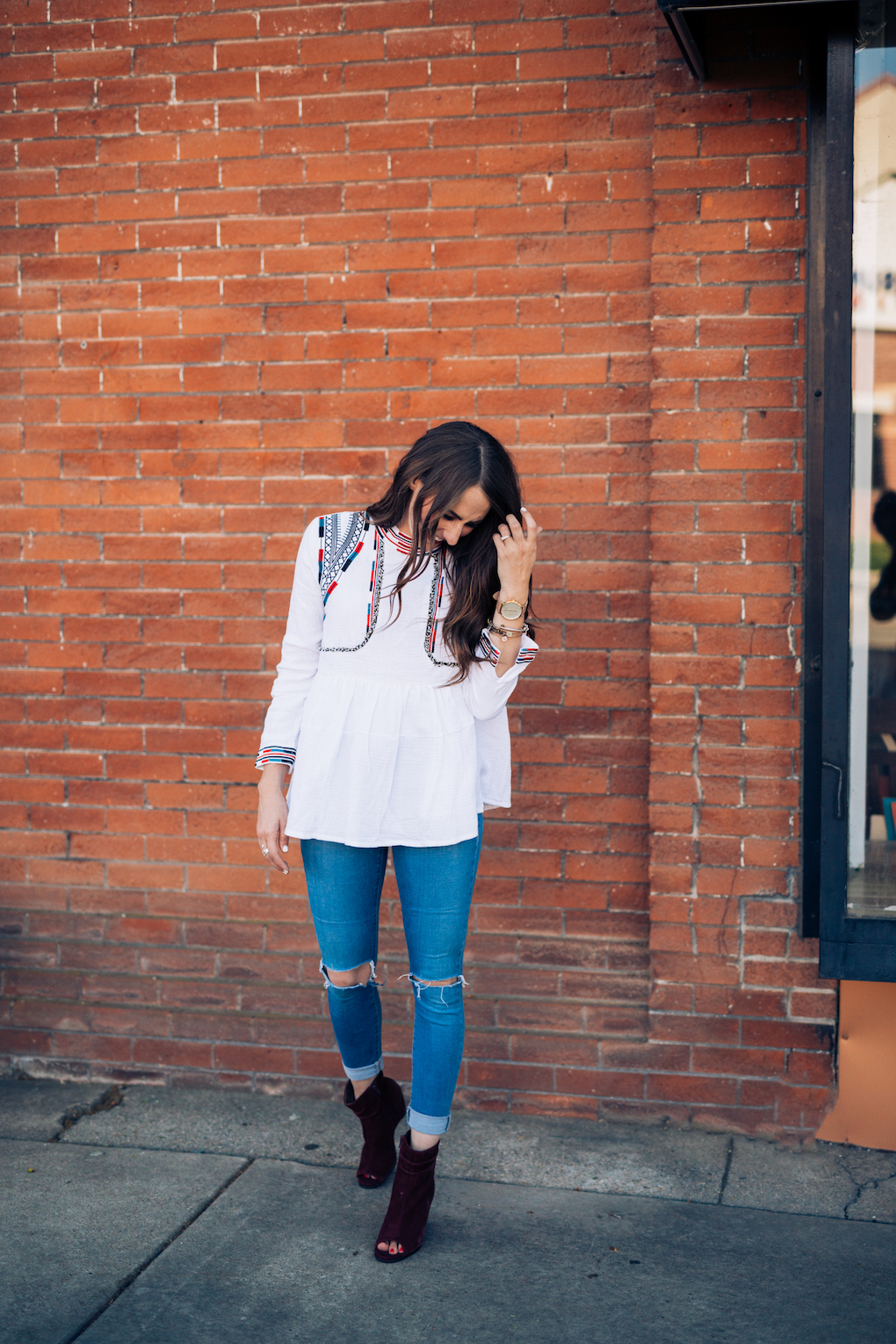 Girl in white peplum top with bright colored embroidery and skinny jeans with maroon booties in front of red wall