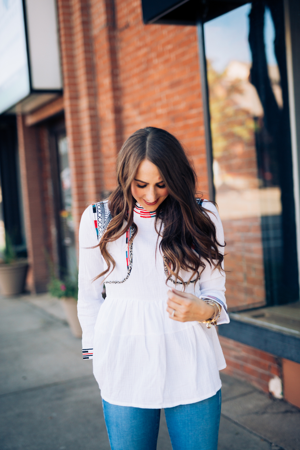 Girl in white peplum top with bright colored embroidery and skinny jeans with maroon booties