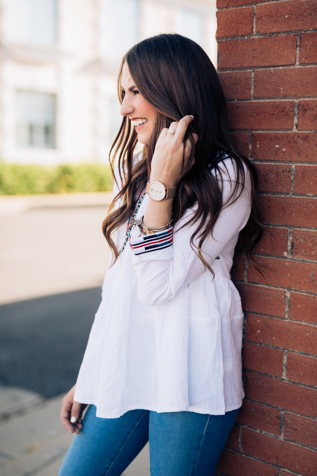 Girl in white peplum top with bright colored embroidery and skinny jeans with maroon booties and arvo watch with alex and ani bracelets