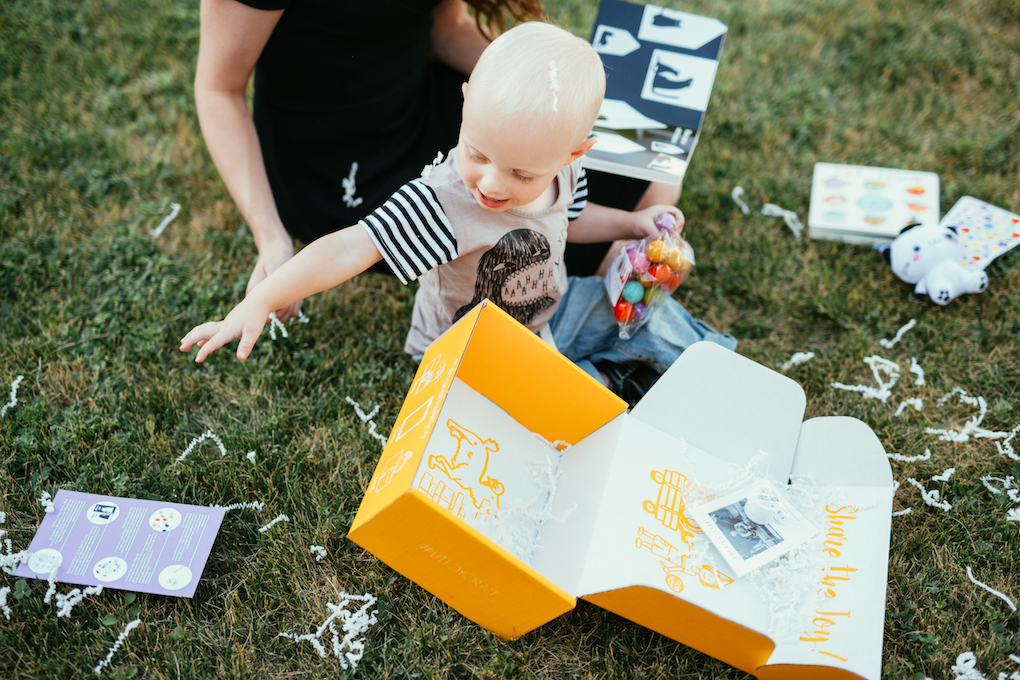 Mom and little boy opening up book subscription box on the grass