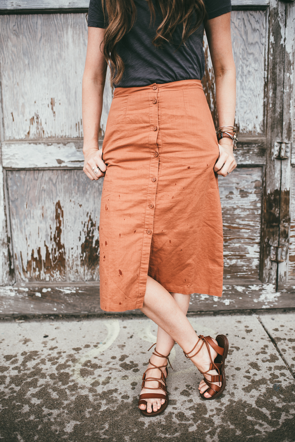 orange button up skirt paired with grey top and brown sandals