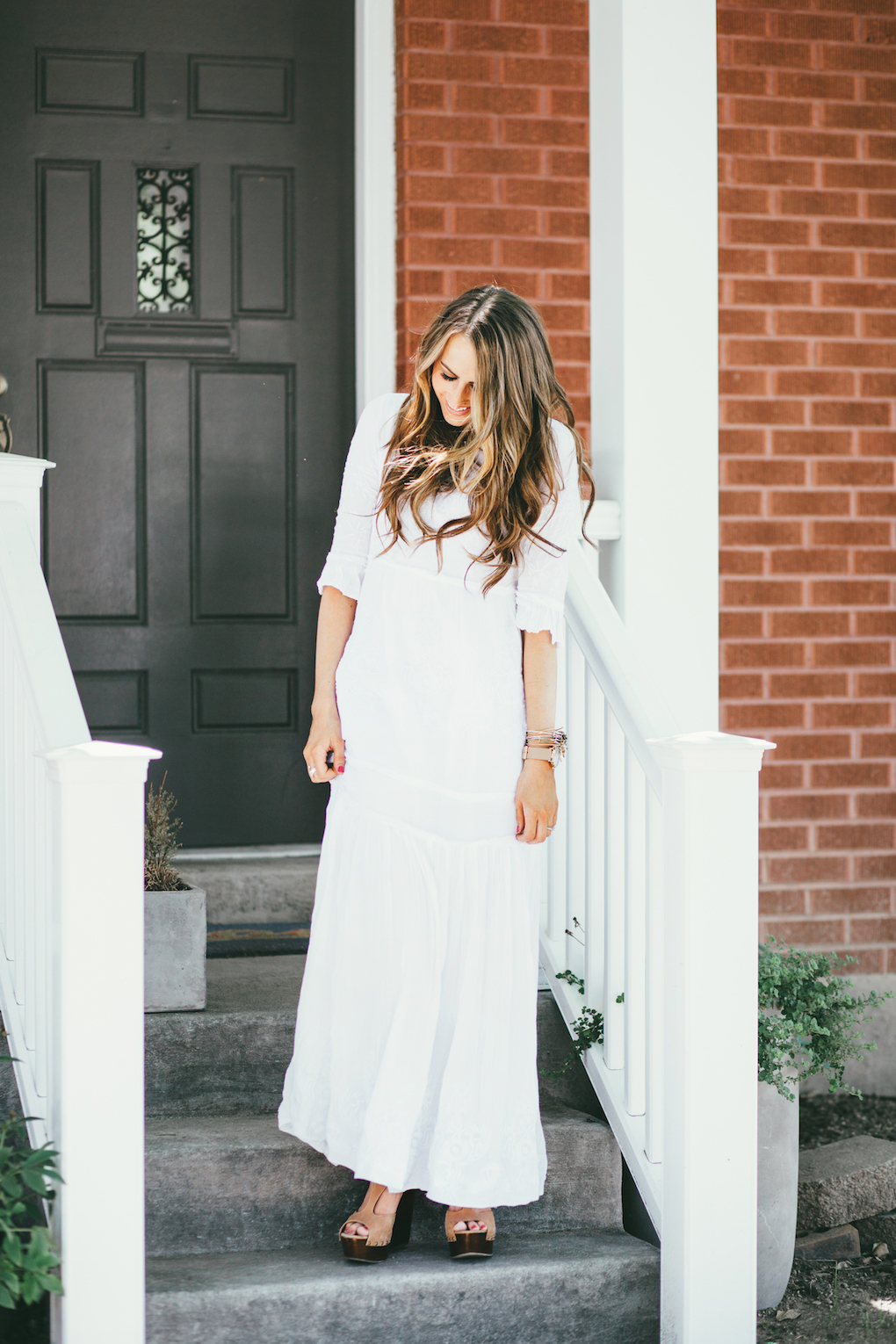 Girl in long white embroidered maxi dress with long loose caramel and brown curls