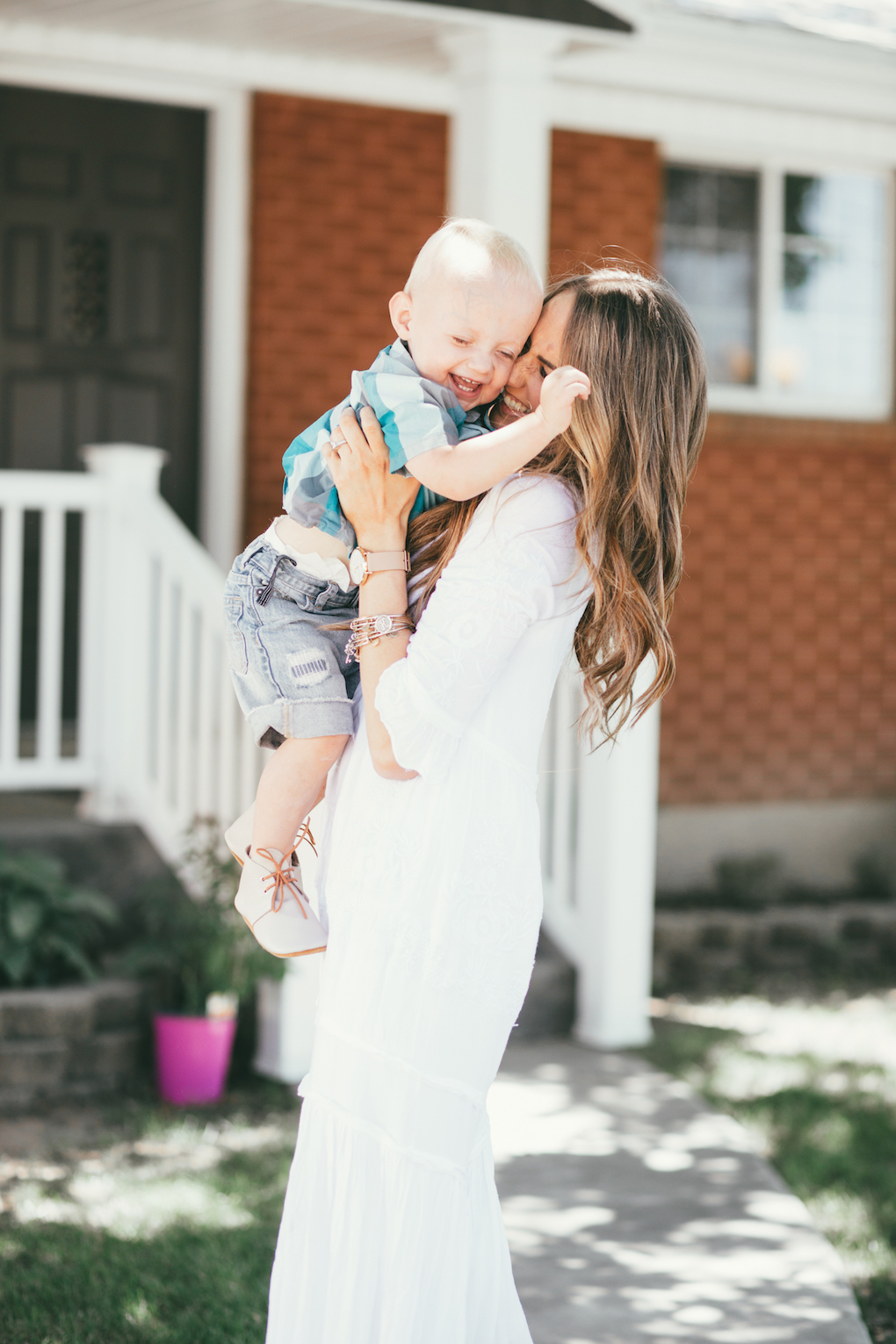 mom and little boy standing in front of red brick house mom wearing white maxi dress with long brown hair loosely curled and blonde highlights little boy wearing turquoise button up with cut off shorts and mon petite shoes