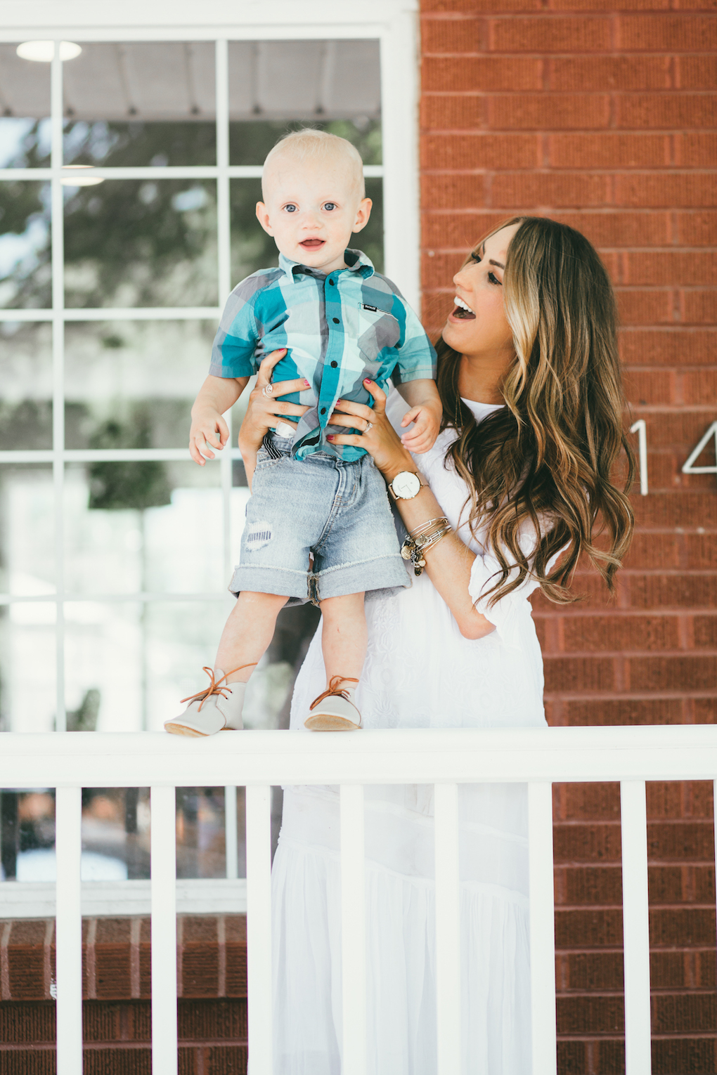 Mom and little boy sitting on porch steps mom wearing white embroidered maxi dress with long loose caramel curls little boy in blue and turquoise plaid shirt and cut off shorts