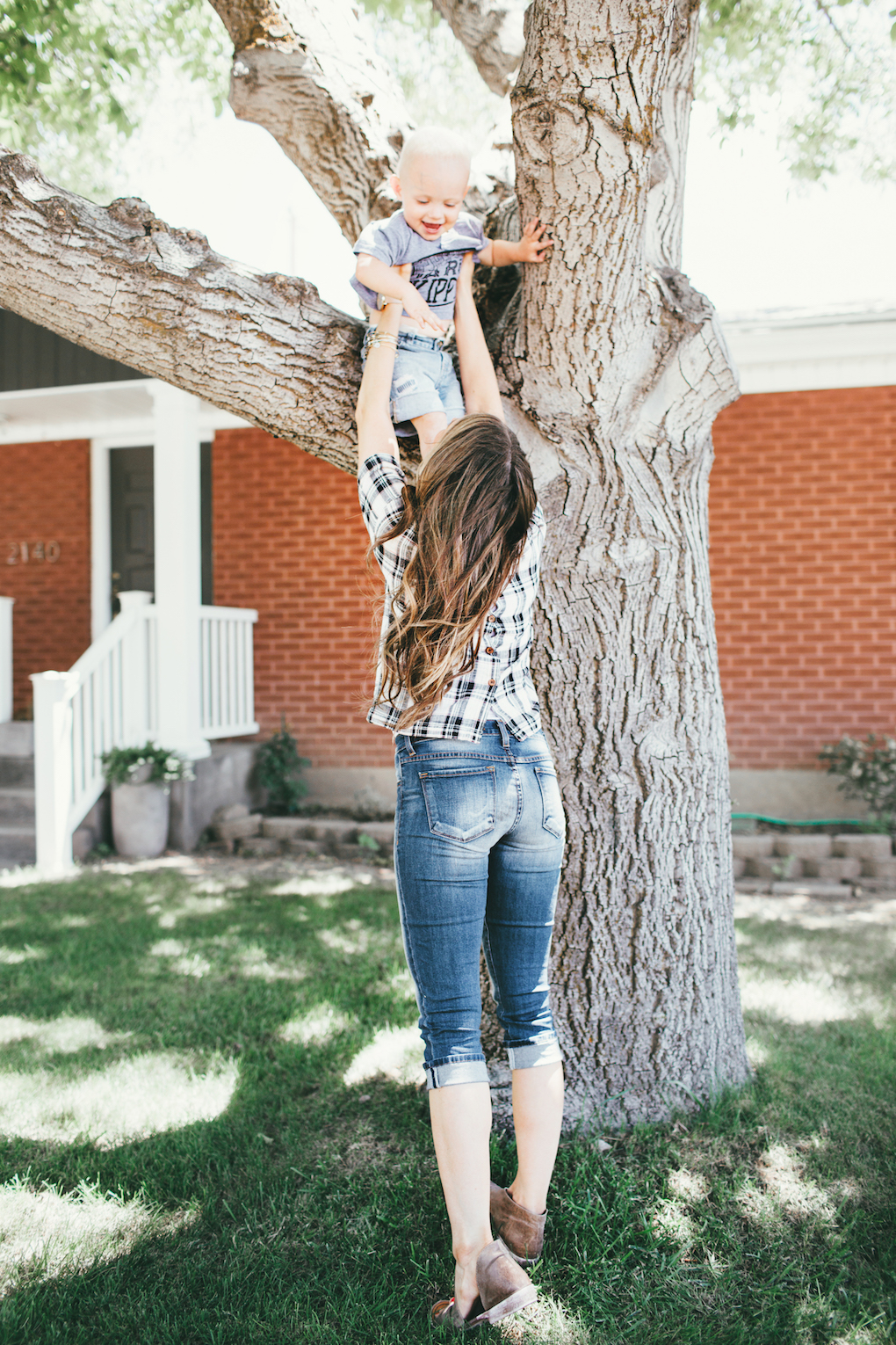 Little Boy in Grey Tee Shirt wearing denim cutoff shorts and mon petite shoes playing with zoli snack container with his mom wearing a plaid short sleeved top, crops, and brown loose curls playing with little boy in the tree