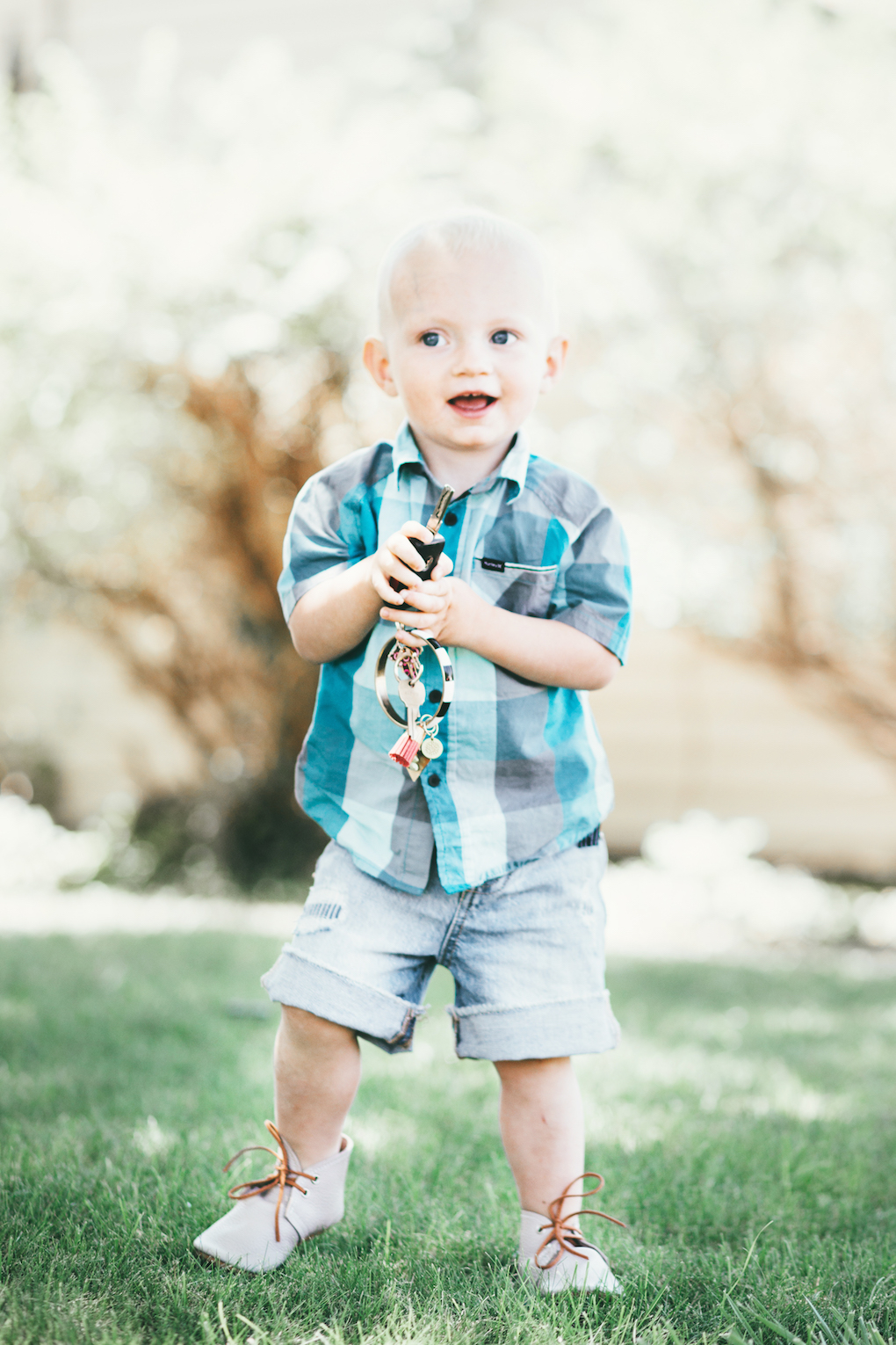 blonde little boy playing on the grass with keys wearing a checked turquoise button up shirt, cut off shorts, and mon petite shoes