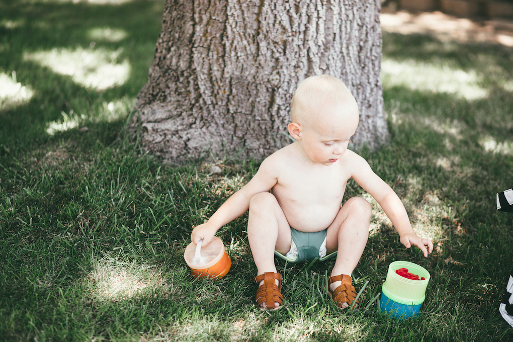 Little boy sitting by tree in short swimmers holding treat container