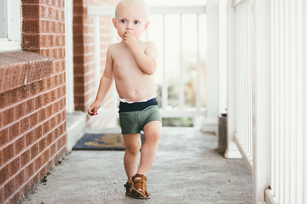 Little boy standing on porch with green short swimmers on