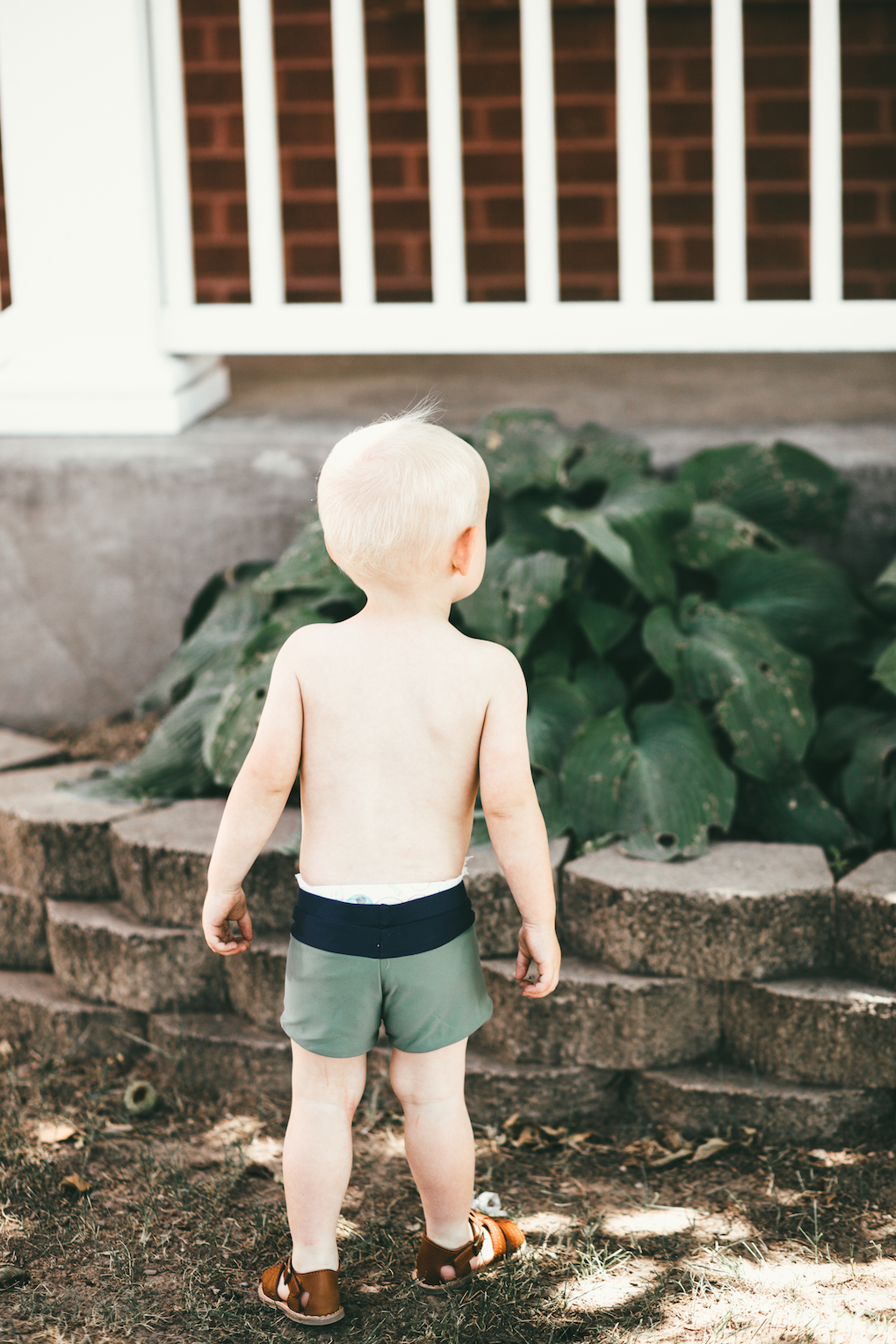 Little boy wearing short green swimmers standing backwards