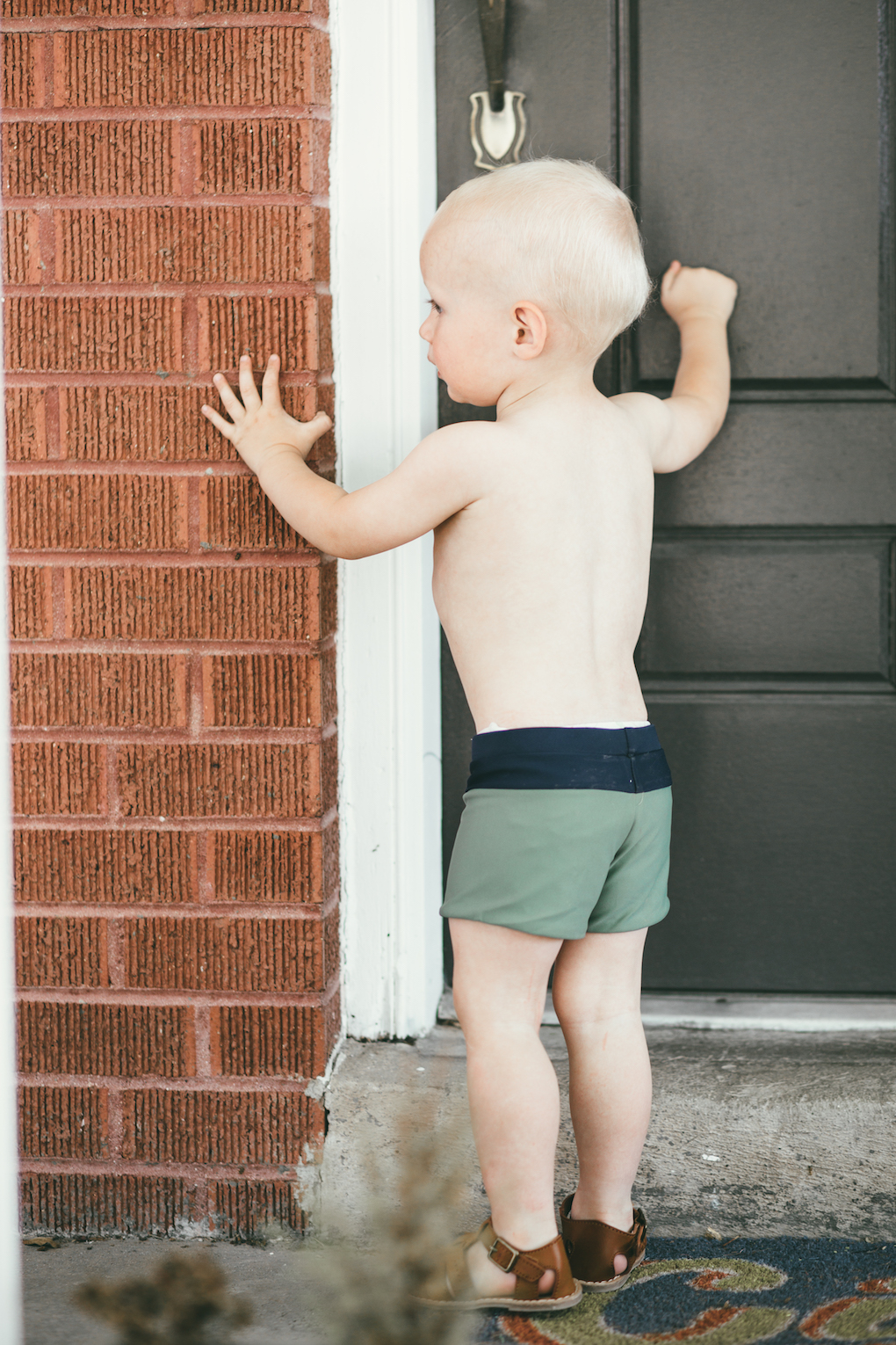 little boy wearing green swimmers knocking on the door