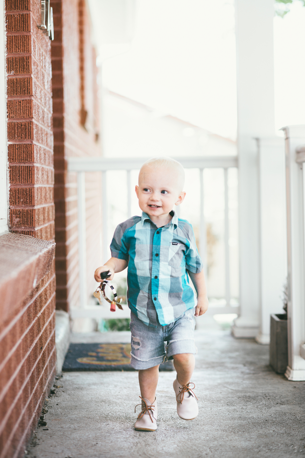 blonde little boy playing on the cement with keys wearing a checked turquoise button up shirt, cut off shorts, and mon petite shoes