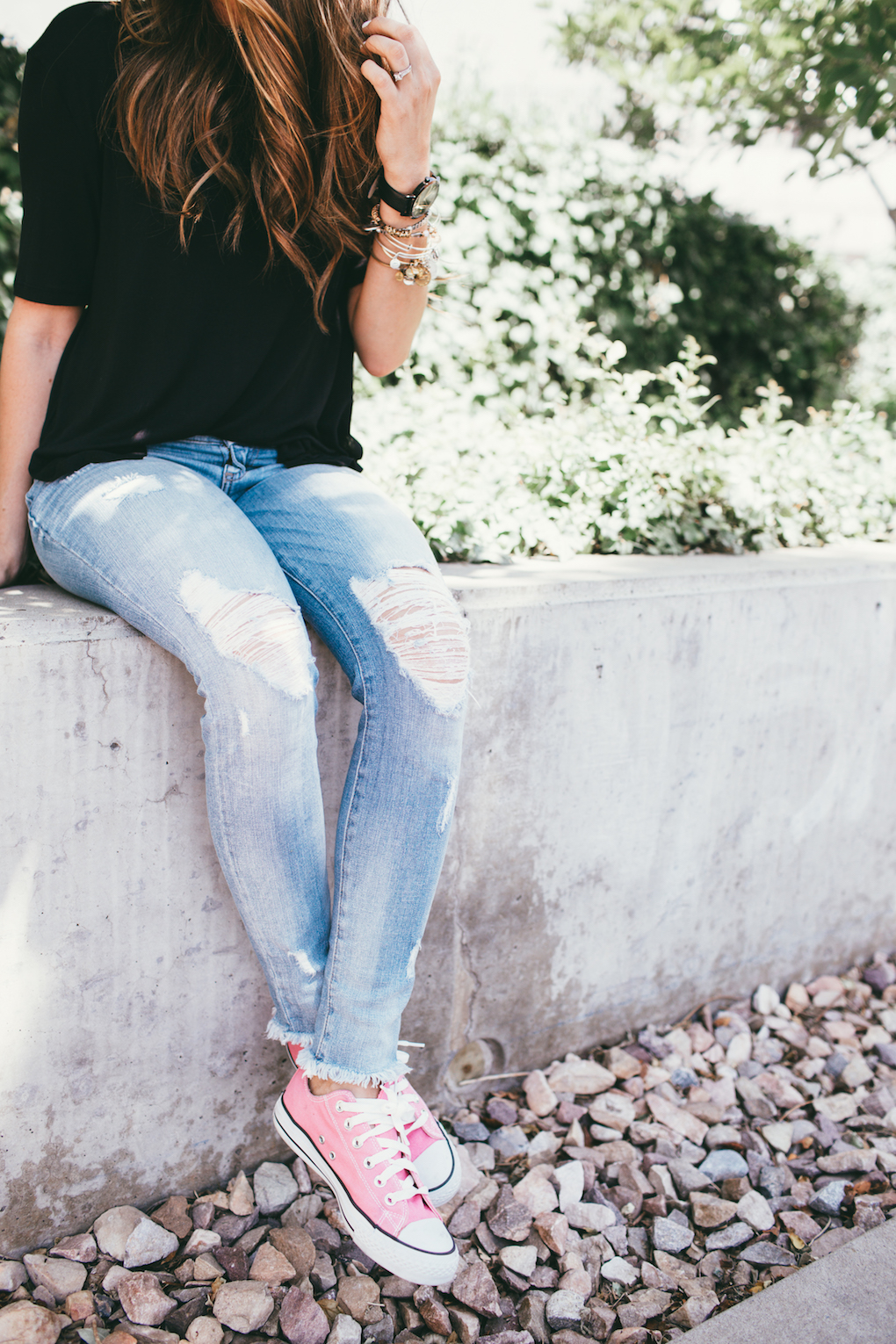 Girl in distressed denim jeans and oversized black tee shirt with loosely curled hair and pink converse