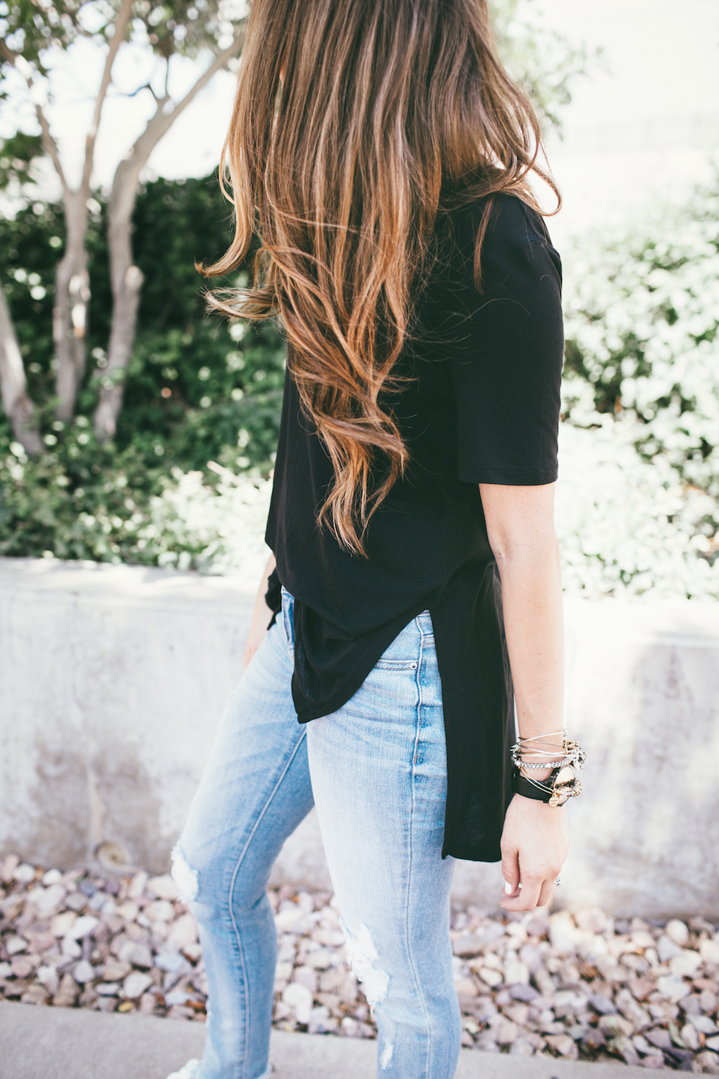 Girl in distressed denim jeans and oversized black tee shirt with loosely curled hair