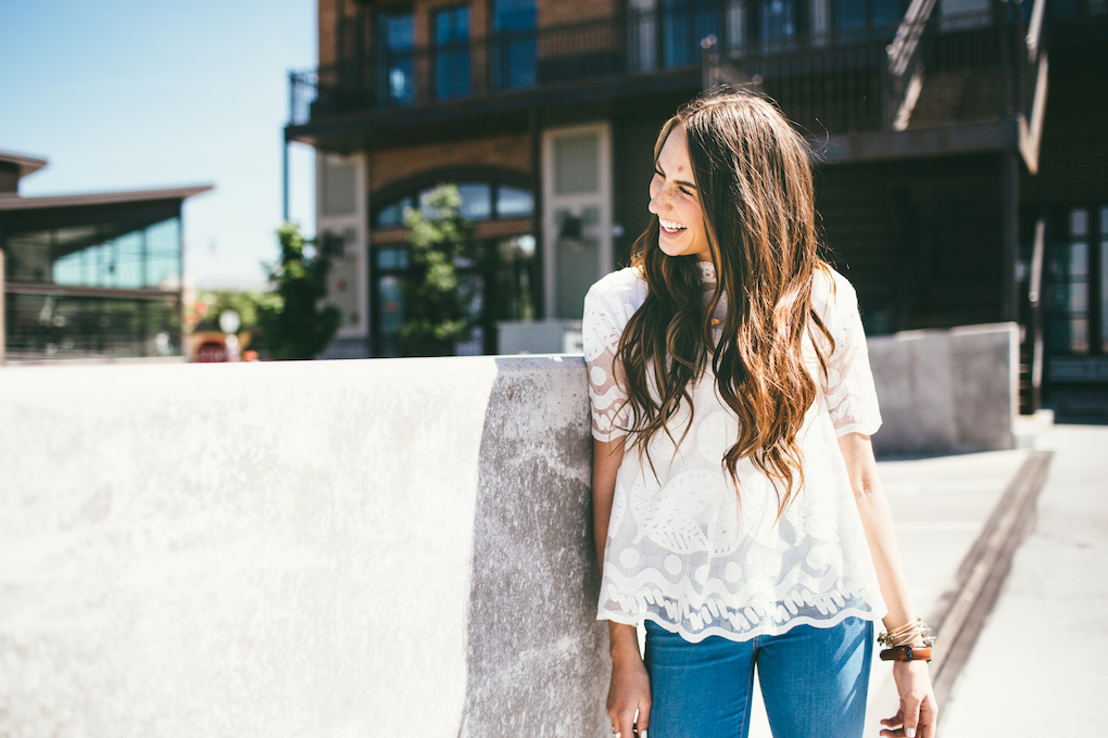 Girl standing in distressed denim jeans free people brown sandals and anthropologie white lemon lace top with long brown hair loosely curled