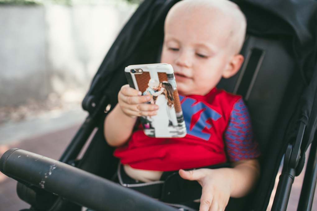 Little boy in red Nike shirt sitting in stroller holding phone in personalized phone case