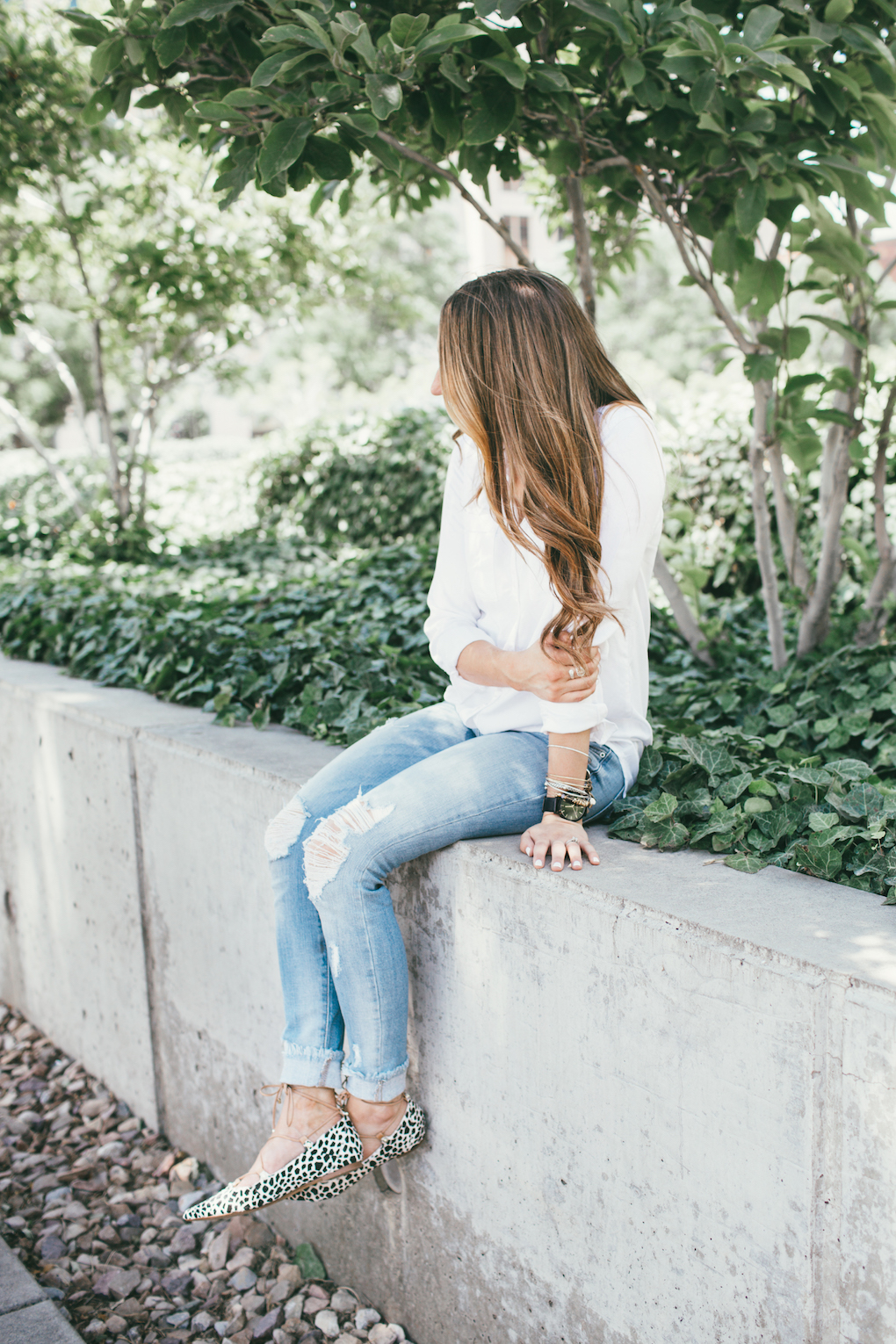 Girl wearing white button up with long loose brown curls and skinny distressed denim