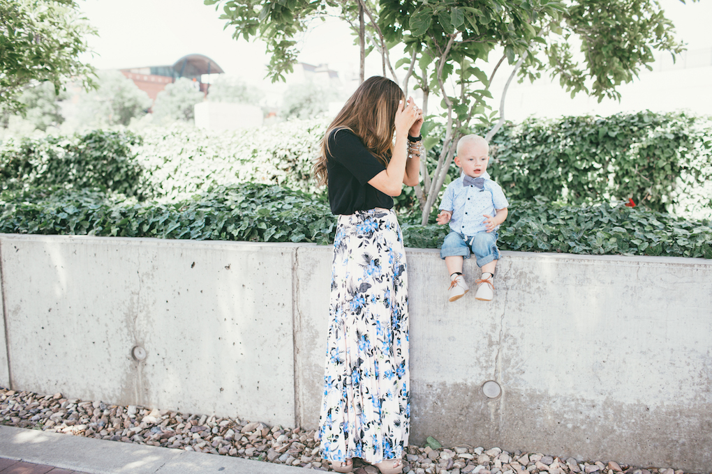 Mom and little boy in dress clothes or sunday best standing outside mom in floral pleated skirt with black top little boy in painter pants and hurley button up with baby bow tie