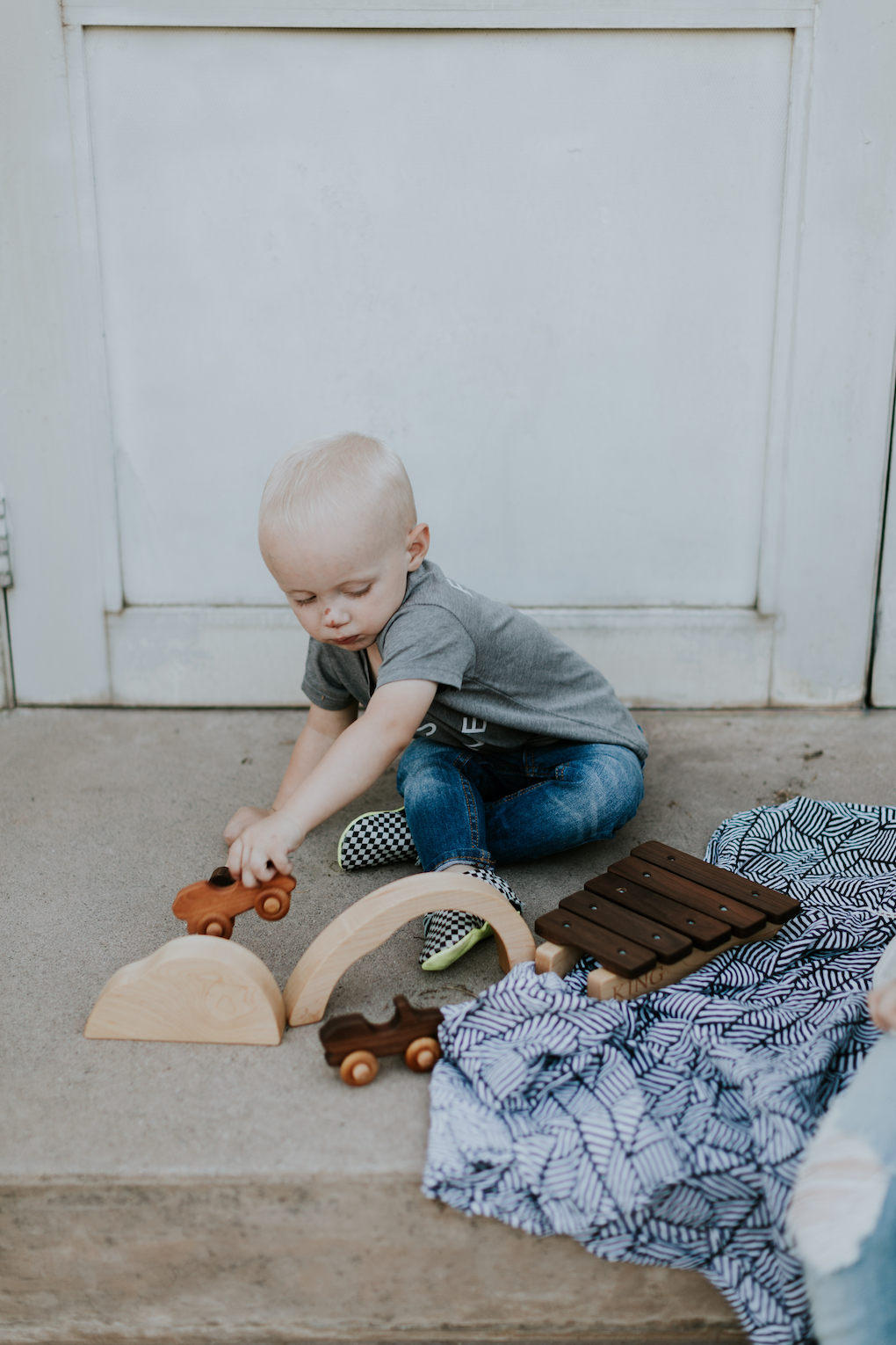 Little boy playing on cement on Captain Silly Pants swaddle blanket with wooden toys wooden car set wearing grey graphic tee skinny jeans and freshly picked moccs
