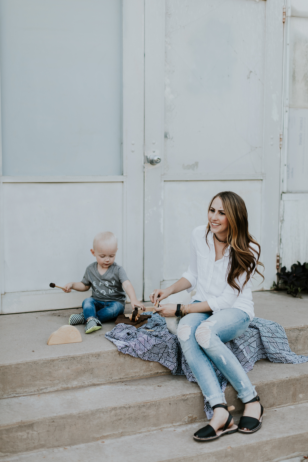mom and little boy playing on stairs with captain silly pants swaddle blanket wooden toys wooden car mom wearing white button up top with skinny distressed jeans and pons little boy in grey graphic tee skinny distressed denim and freshly picked moccasins