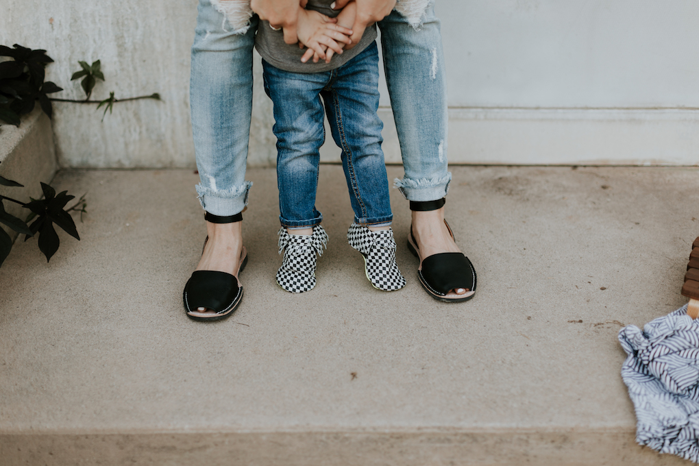 little boy in skinny distressed denim and black and white checked freshly picked moccasins with mom in distressed denim and pons shoes
