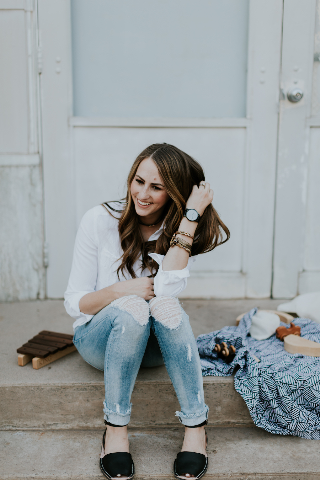mom sitting on steps with captain silly pants swaddle blanket and wooden toys wearing white button up shirt arvo black watch alex and ani bracelets with choker on and distressed denim with pons shoes