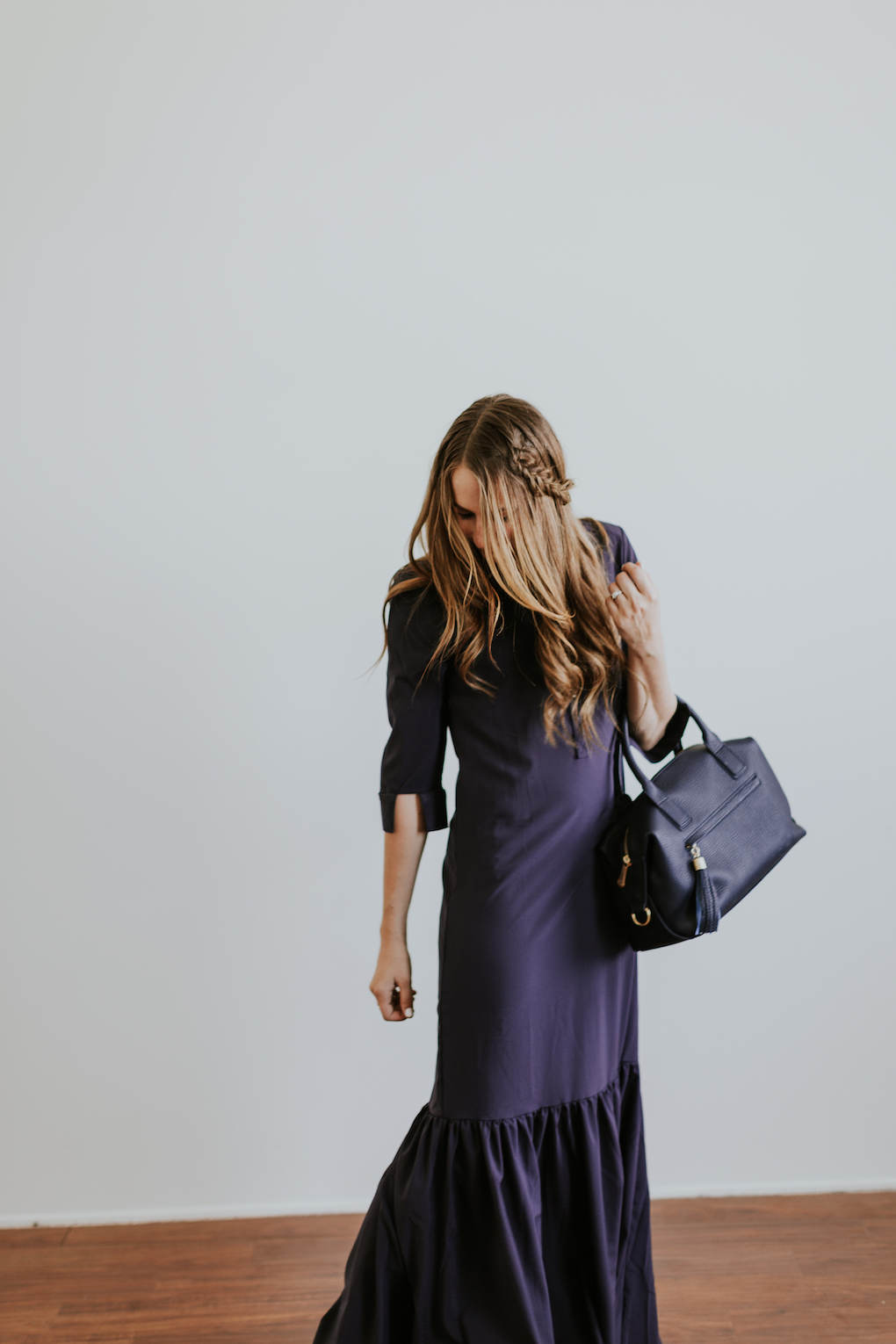 Girl with fishtail braid wearing long navy maxi dress with ruffle and a navy gigi new york bag