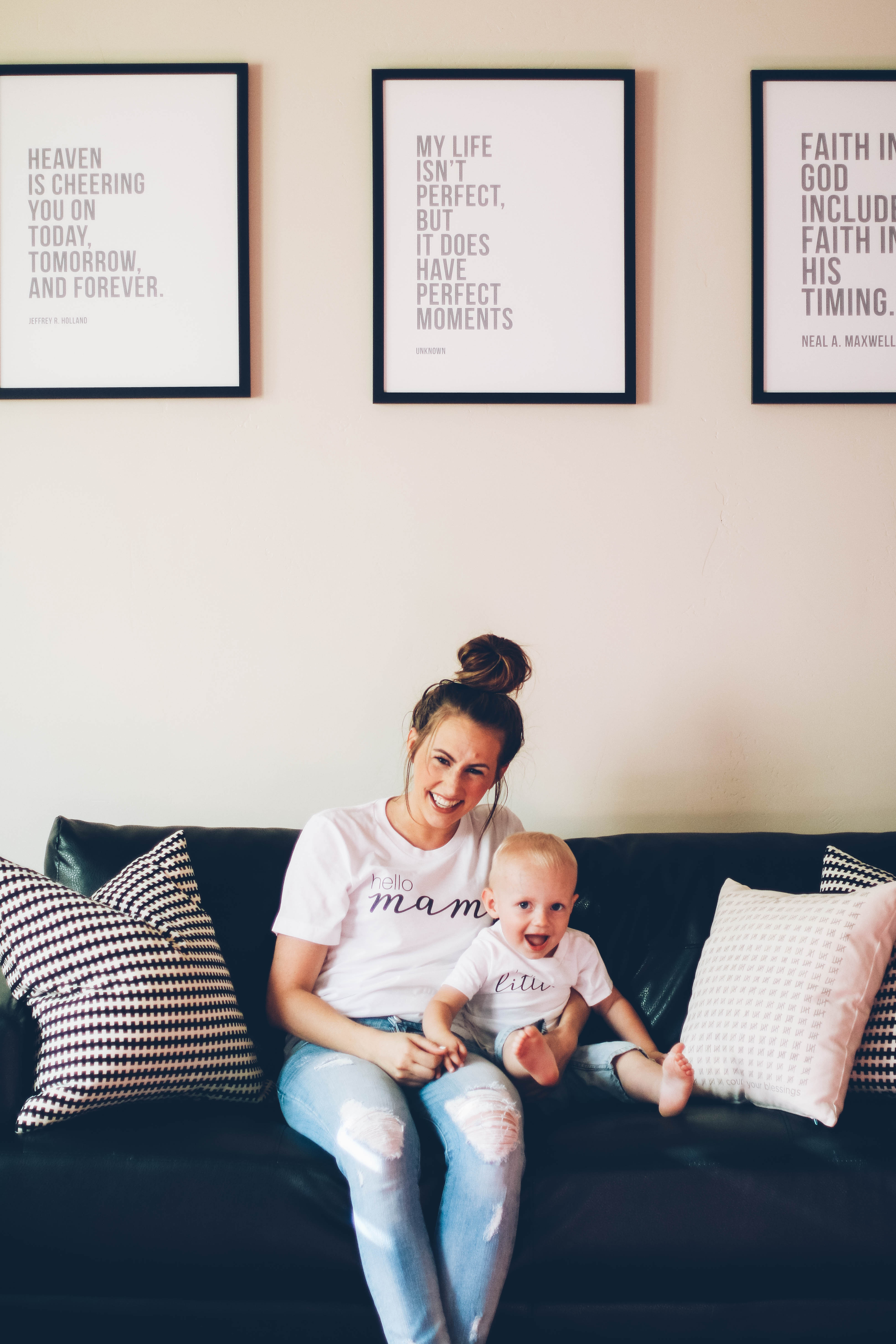Mom and little boy sitting on modern black leather couch with lds framed prints on wall and ruby claire white tee shirts on with denim shorts and denim skinny jeans