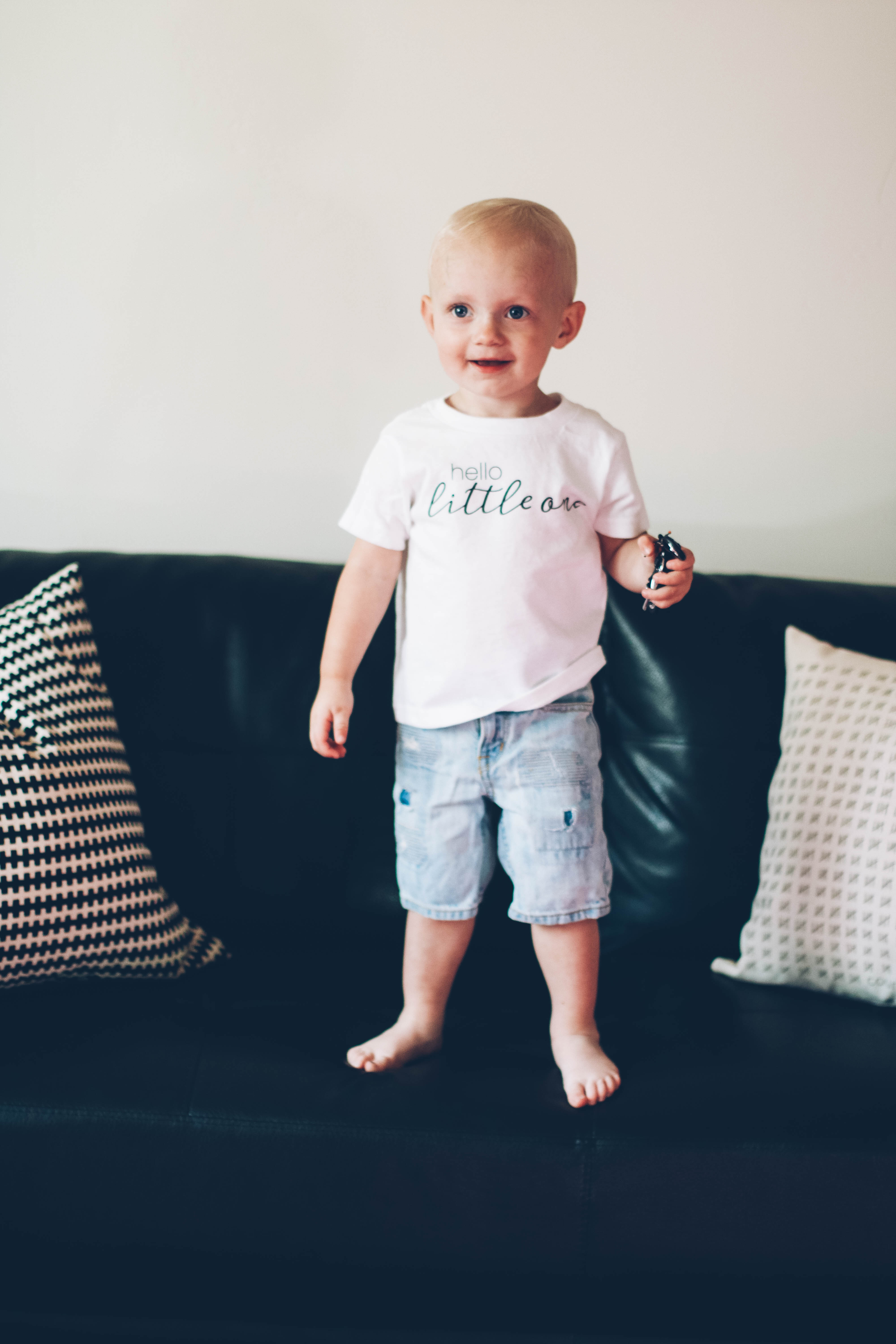 little blonde boy in hello little one white basic tee standing on modern black couch in cutoff shorts