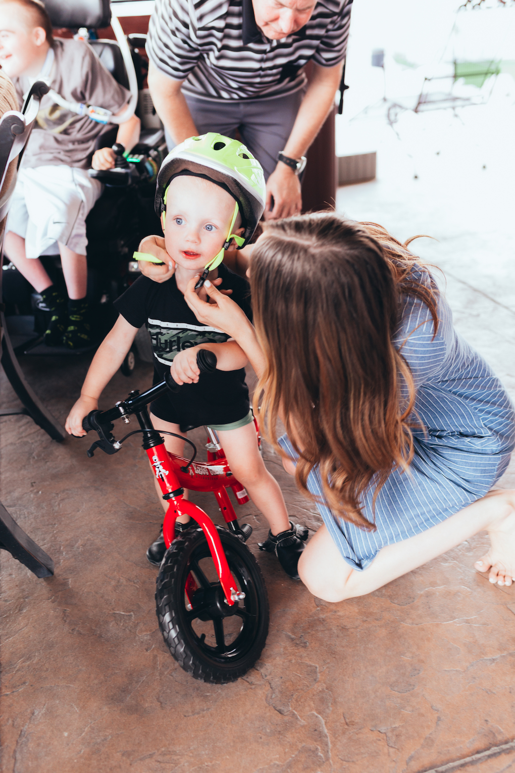 KINGS HAPPY UN-BIRTHDAY - KIDS BALL PARTY by Utah blogger Dani Marie - Toddler riding red balance bike with bright green helmet on