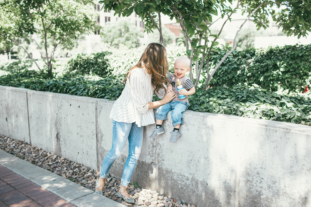 Mom in white stripe peplum black choker and distressed denim little boy wearing rags to raches tee shirt with rolled up denim and freshly picked moccs