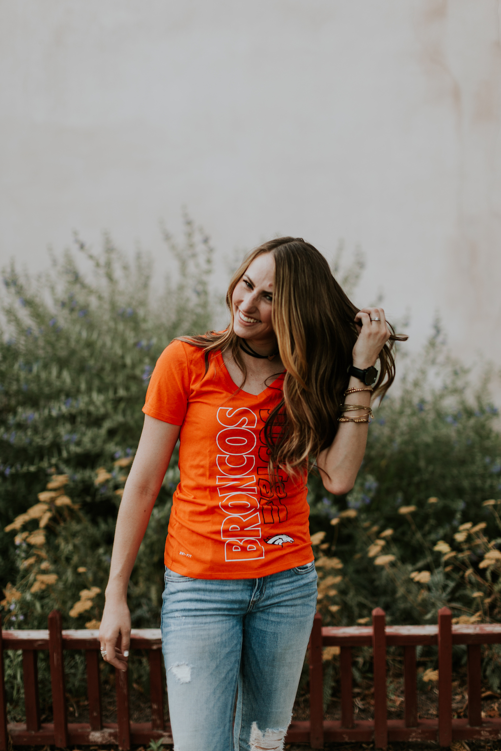 Womens NFL Broncos T-Shirt girl wearing bright orange Broncos Tee shirt with brown curled hair and skinny distressed denim